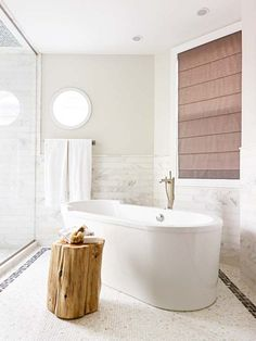 Free standing modern tub, flat roman shade and wood stump end table in white bathroom