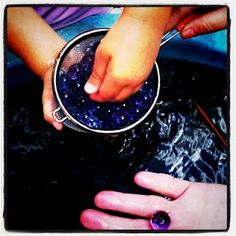a strainer and a water table filled with water beads and water - add aquamarine and gold beads for treasure