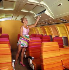 The Elegant 1971 High Wide and Handsome Wide Body Interior for Boeing 727 Aircraft and Hostess is Wearing 1971 Emilio Pucci Pant Dress Collection Uniform
