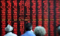 Investors look at stock information at a trading hall in a securities firm in Shenyang, north-east China, on Friday.