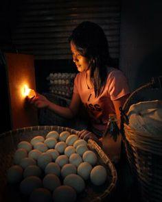A woman holds an egg under a light.