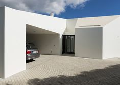 Four small blocks fan out from the facade of this white concrete house on a Portuguese island.