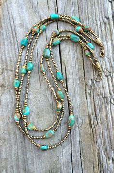 """Three strands of hand beaded Czech glass seed beads, stunning blue green turquoise, and antiqued brass accents. Approx 17"""" in length as shown, may be adjusted upon request."""
