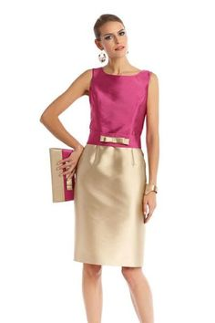 Vestido de madrina corto en color fucsia-crema. Falda recta con lazo ornamental en cintura. Lleva torera fucsia a conjunto.