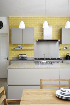 The kitchen was designed by SieMatic and the pendant lights are by Flos from Minima. The mustard tiles are from Fired Earth.
