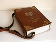 This bag is made in a shape of a book, inspired by Neverending Story  = Exterior = Made by genuine leather. Adjustable strap 124 cm maximum length