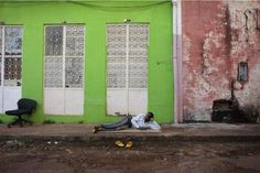 A security guard relaxes in front of colonial-era buildings in Guinea-Bissau's capital Bissau October 31, 2012.  REUTERS-Joe Penney