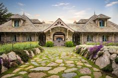 French Normandy style home with stone and moss driveway, and Dutch doors opening into an entrance courtyard.