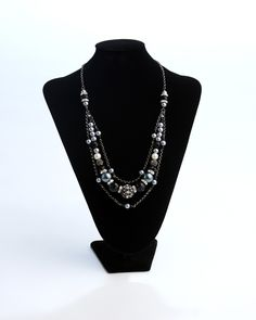 Vi Bella Jewelry - Midnight Necklace - A night out? A night in? Do both in style! The triple strand Midnight Necklace consists of a large rhinestone bejeweled bead, multifaceted black beads, gray and ivory pearls and sparkly rhinestone and silver spacers, all on delicate gunmetal chains.  Wear with Midnight Earrings and Midnight Bracelet to achieve a truly elegant look.     Length - 24 - 26 Inches      Handcrafted by Vi Bella Artists in Haiti.  $44.95