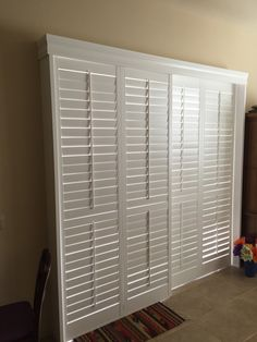"Open by-pass shutter over a large sliding glass door. 3 1/2"" louvers White wood shutter. With center divider rails. Traditional tilt bar. With decorative balance."
