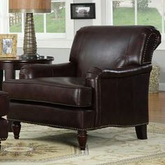"""Wood-framed arm chair with dark brown bonded leather upholstery and nailhead trim.     Product: Chair   Construction Material: Solid wood and bonded leather Color: Dark brown  Features:   Back cushions attached Brass nailhead detail     Dimensions: 33.5"""" H x 33"""" W x 38"""" D"""