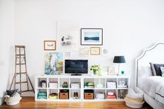 A small gallery wall around a mounted TV on bookshelf