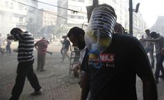 A member of the Muslim Brotherhood and supporter of ousted Egyptian President Mohamed Mursi wears a makeshift gas mask as others run away from shooting during clashes in front of Azbkya police station during clashes at Ramses Square in Cairo August 16, 2013. REUTERS-Amr Abdallah Dalsh