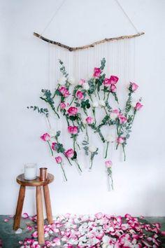 Pared decorada con flores colgando de un rama #decoración #floresartificiales