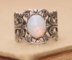 Een prachtige verstelbare band ring gemaakt met behulp van een vintage pinfire opaal. De opaal glas is wit van kleur met gebieden van gele of