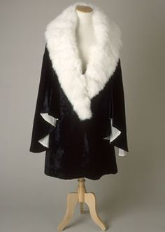 1930-36 evening coat of black silk velvet lined with white silk crepe de chine. Deep shawl collar of white angora rabbit fur.