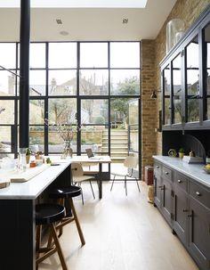 industrial kitchen - steel windows, raw brick walls, salvaged pillar - with elegant marble work surface and dark grey cupboards