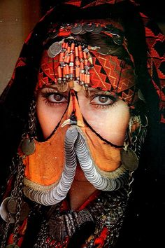 A woman modeling what I believe is an antique Bedouin face veil from Jordan, and an antique kirdan necklace of the style made in Kerak and Nablus.  Gorgeous ensemble!