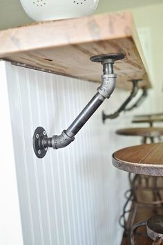 Industrial pipes holding up a solid wood bar in the kitchen. Pipe Shelf Brackets, Pipe Shelves, Basement Flooring, Pipes, Trumpets