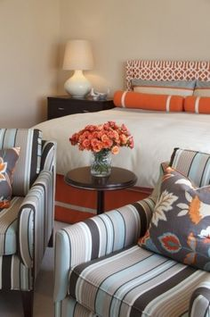 Like the orange gray and blue colors together... Orange color pop with the gray... The striped chair coupled with floral print in same color scheme. Tasteful orange accent... orange and grey... orange grey bedroom...