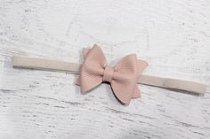 Blush leather bow attached to taupe velvet elastic - or you can opt to have the pink bow attached to a double prong alligator clip. This headband