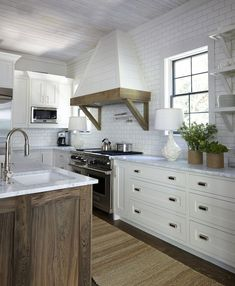 Amazing two-tone kitchen features a stained oak island topped with white marble framing prep sink paired with gooseneck faucet across from stacked shelving over an Arteriors Vagabond Cream Crackle Porcelain Lamp and cork vases filled with plants.