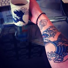 """41 Incredible Tattoos Inspired By Works Of Art // This tattoo is a copy of a famous piece of ancient Chinese art, """"The Great Wave off Kanagawa,"""" by Hokusai. Also shown on coffee mug. The blue is so intense!"""
