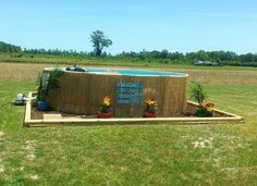 """Well, we decided to spruce up our Wal-Mart pool!  We went to our local Home Depot, where we purchased the Reed Fencing, some landscape timbers, mulch and flowers.  We cut the Reed Fence down to size (can cut with shears), laid out the timbers, put down some mulch, and planted some flowers.  I got the pots from the Dollar Tree.  Total cost was about $200...we also added a little sign """"Welcome to our Redneck Swimmin' Hole"""", for fun.  We now have a little """"tropical"""" oasis in our backyard! Landscape Timbers, Reed Fencing, Tiki Bar Signs, Pool Storage, Above Ground Pool Landscaping, Pool Care, Intex Pool, Outdoor Ideas"""