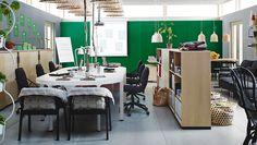 Espacio de trabajo abierto con mesa de reuniones de chapa de abedul/gris plata y estanterías abiertas y cerradas