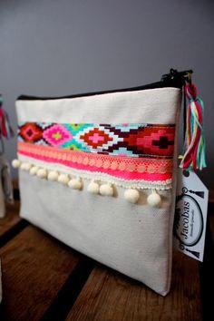 Pochette brodée avec du ruban de designer multicolore et des pompons bancs . Ce produit à été réalisé à la main dans notre atelier situé à Colmar, en France.