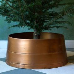 """A sleek replacement for traditional fabric skirts, this copper circlet makes a distinctive base for your holiday tree.- Galvanized iron, copper finish- Indoor or outdoor use- Imported10""""H, 21"""" diameter at top, 24"""" diameter at base"""