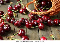 Ripe cherries on a wooden table, food close up by Olha Afanasieva, via Shutterstock.