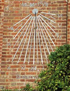 Vertical sundial by David Harber. These sundials comprise strips of bronze, brass, copper or stainless steel attached directly to the surface of the wall. The numerals and sundial furniture are laser cut to match.