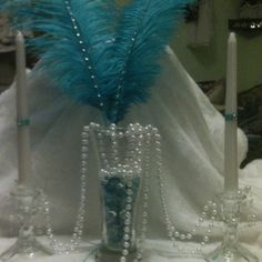 Rhinestoned feathers in $1 beer glass, pearls, white candles with ribbon and stones from a bracelet on  $1 glass candleholders. Very elegant, 1920's look for centerpieces and inexpensive.