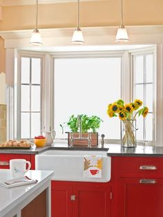 A farmhouse sink by Rohl is framed by cheery red cabinets and a bay window. | Photo: Monica Buck