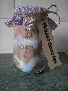 Pickled Grannies!!  individually hand crafted faces (with blue and purple hair rinse!!) crammed together into a glass jar.