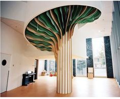 studio millimètre installs six meter high tree in paris nursery the monumental interior element is made of plywood boards, with leaves composed of suspended, cut paper sheets. Tree Interior, Interior Columns, Interior Architecture, Interior Design, Ceiling Design, Wall Design, House Design, Paris Nursery, Kindergarten Design