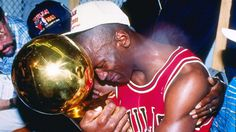 An iconic image of Michael Jordan holding the recently won championship trophy. The reason he is crying is because his dad was shot to death earlier in the season.