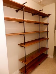 Full wall shelves made with black iron pipe and reclaimed cedar, custom made handcrafted full wall shelving unit