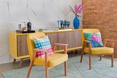 Decoração de apartamento colorido, móvel amarelo, com vaso azul com flores, taças azuis, parede de tijolinho, poltrona amarela.