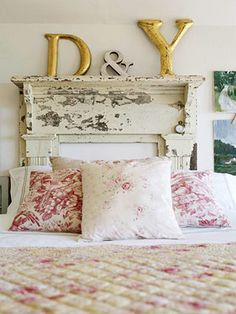 In place of a headboard, a salvaged mantel gives this bedroom architectural flair. The more distressed the better for a vintage look like this.