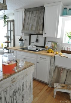 This whole kitchen is amazingly gorgeous.  I really like the weathered wood range hood.