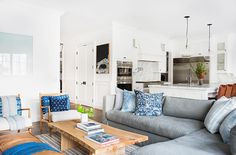 A gray sectional in white living space with wood coffee table
