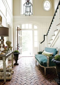 Classic and cool converge in the entry hall with herringbone brick flooring, a painted Louis XVI console and a brightly colored settee--love the floors, reminds me of my Aunt Lori's house!