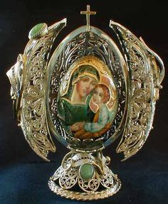 Faberge style egg - that opens to display a mini-icon of Mary & Baby Jesus - designed after the Carl Faberge masterpieces from St Petersburg Russia. Decorated with semi-precious stones and crowned with a cross.
