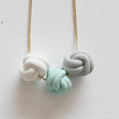 Polymer Clay Love Knot Trio Necklace handmade by me! Available in baby pink, lilac, light grey, mint and white. I carefully mix the polymer clay to blend beautiful colours and shape and decorate. Each clay knot is approx 2cm in diameter and is strung on an 18inch gold or silver plated snake chain