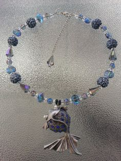 This is a 16 inch pisces (fish) choker necklace. It can be made in to any size. Just message me. It is made up of blue, blue ab, clear glass beads, shiny blue beads and a silver fish pendant with blue crystals.