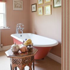 This elegant bathing space, with its striped wallpaper and roll top bath takes inspiration from classic hotels and gentleman's clubs. The peach palette updates the more traditional pink.
