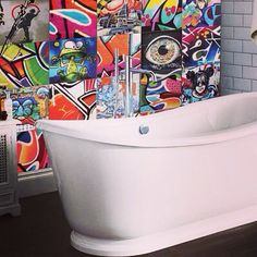 Mix of streetart and graffiti tiles to create this vibrant feature wall in the bathroom. The rest of the bathroom has been tiled with subway style tiles and a wooded floor. Love the design, great bathroom!