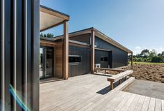 Robust metal cladding on the weather prone sides of the home. Cedar cladding contrasting against Black Vertical Metal Cladding. Black aluminium joinery with Colorsteel longrun roofing. Auckland Waikato Coromandel
